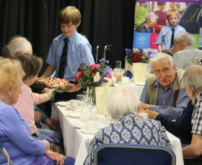 Children from Kew College serve afternoon tea for their guests from Kew Neighbourhood Association